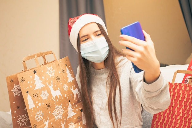 Une jeune femme portant un masque médical et une casquette à la maison félicite ses amis pour noël et le nouvel an via un smartphone, le père noël