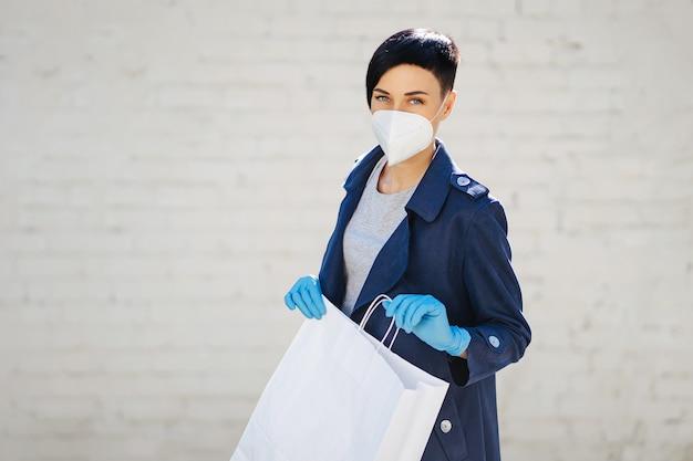 Jeune femme portant un masque médical jetable et des gants tenant un sac en papier avec des achats pendant l'épidémie de covid 19. concept de service de livraison.