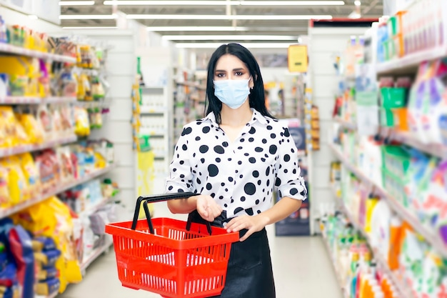 Jeune femme portant un masque médical jetable shopping dans un supermarché pendant l'épidémie de pneumonie à coronavirus. protection et prévention des mesures pendant le temps de l'épidémie.