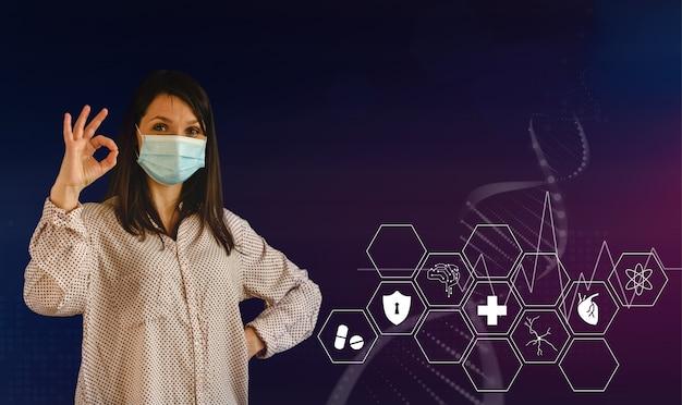 Jeune femme portant un masque médical montrant le signe ok antécédents médicaux avec des icônes et des symboles