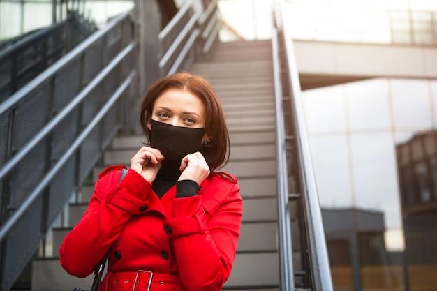 Une jeune femme portant un masque médical de protection noir près d'un bâtiment en verre avec un escalier dans un manteau rouge