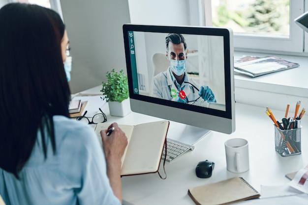 Jeune femme portant un masque protecteur parlant au médecin par appel vidéo