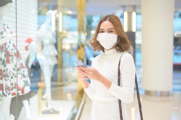Une jeune femme portant un masque de protection dans un centre commercial, faisant du shopping sous le concept de pandémie de covid-19.