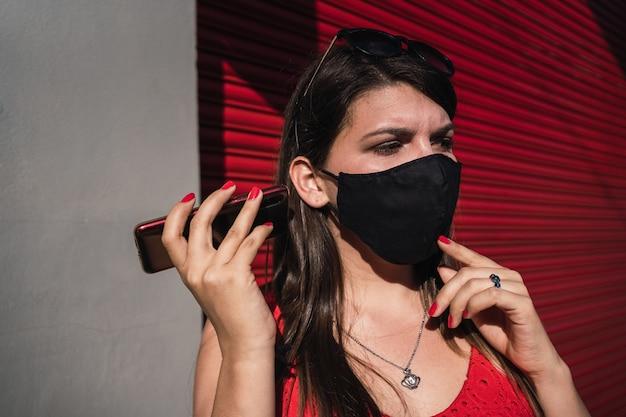 Une jeune femme portant un masque de protection utilise un téléphone intelligent et écoute un message vocal dans la rue urbaine.