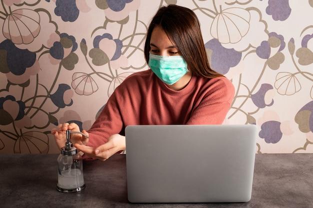 Jeune femme portant un masque, travaillant à la maison et se lavant les mains. concept de coronavirus