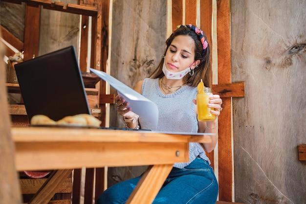 Jeune femme portant un masque et des vêtements décontractés lisant avec un verre de jus.