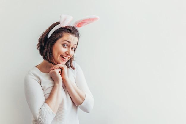 Jeune femme portant des oreilles de lapin isolé sur tableau blanc