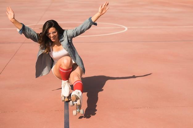 Jeune femme portant des patins à roulettes en équilibre sur le court