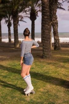 Jeune femme portant des patins à roulettes en regardant la plage