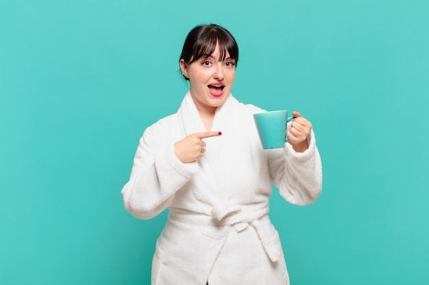 Jeune femme portant un peignoir à l'air excité et surpris pointant vers le côté et vers le haut pour copier l'espace