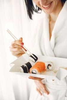 Jeune femme portant des peignoirs, manger des sushis.