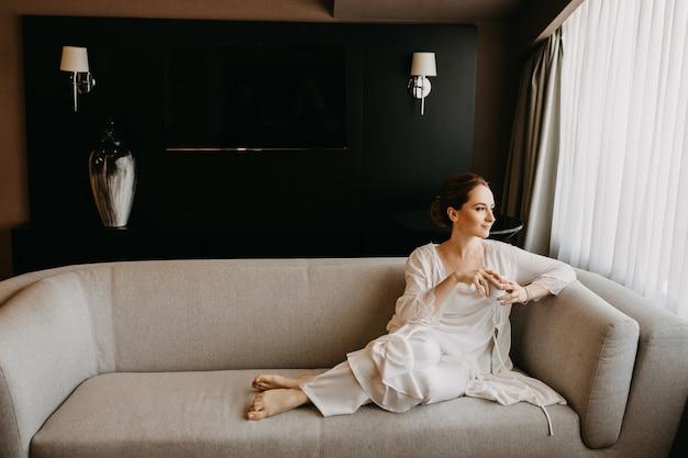 Jeune femme portant un pyjama en soie blanche, assise sur un canapé, tenant une tasse de café.