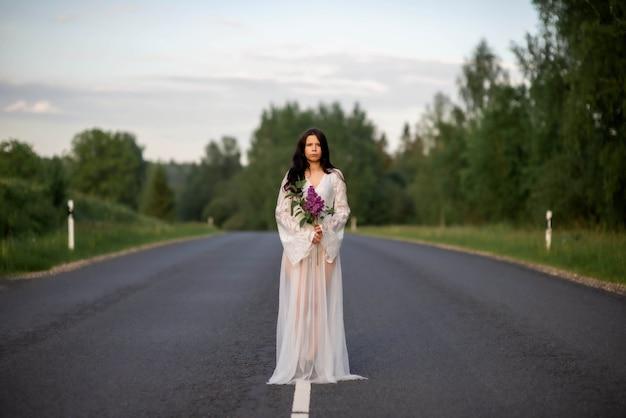 Jeune femme portant une robe blanche tenant une fleur lilas sur une route de campagne vide