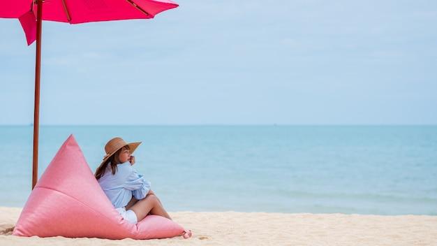 Jeune femme portant une robe bleue élégante et un chapeau de paille avec un ciel bleu sur la plage en thaïlande.