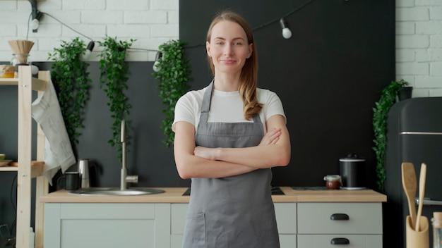 Jeune femme portant un tablier gris souriant et croisant les bras debout dans sa cuisine
