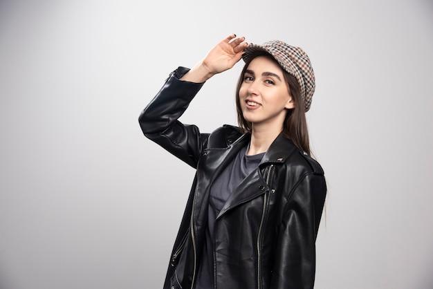 Jeune femme portant une veste en cuir noir et une casquette.