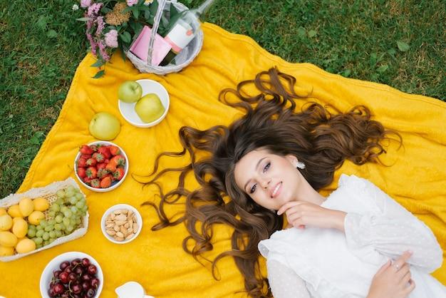 Jeune femme portant des vêtements décontractés ayant un pique-nique avec des fruits le jour d'été.