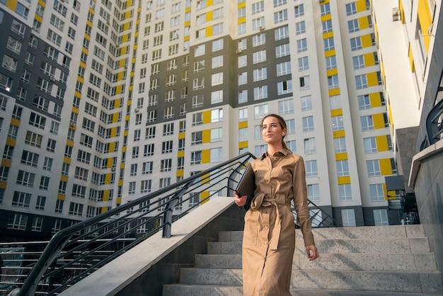 Jeune femme portant des vêtements décontractés tenant un ordinateur portable et descendant les escaliers d'un immeuble de grande hauteur. concept d'entreprise et de mode de vie urbain