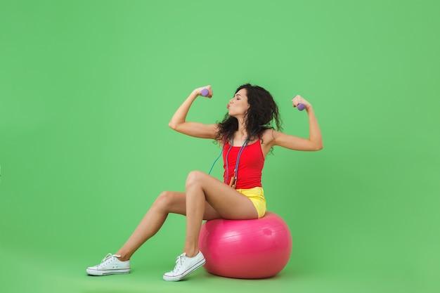 Jeune femme portant des vêtements d'été soulevant des haltères alors qu'elle était assise sur un ballon de fitness pendant l'aérobic contre le mur vert