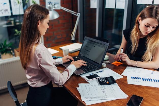 Jeune femme portant des vêtements formels travaillant sur un ordinateur portable en tapant des e-mails assis sur son lieu de travail.