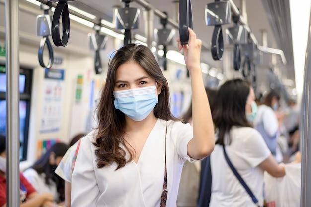Une jeune femme porte un masque de protection dans le métro, la protection covid-19, les voyages de sécurité, la nouvelle normalité, la distance sociale, le transport de sécurité, les voyages sous le concept de pandémie.