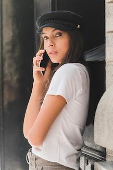 Jeune femme, porter, chapeau noir, parler, sur, téléphone portable