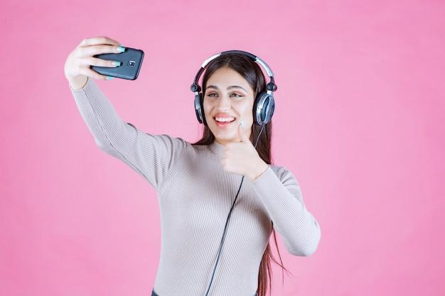 Jeune femme, porter, écouteurs, et, prendre, elle, selfie