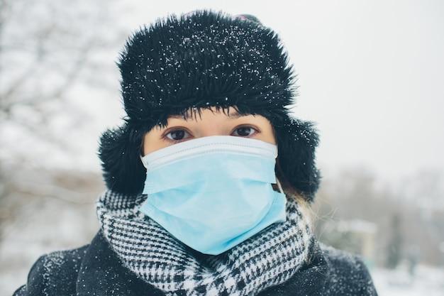 Jeune femme, porter, masque facial, pour, maladie, coronavirus, protection. portrait de femme concentrée sérieuse regarder directement sur la caméra. rester à l'extérieur. préparez-vous à vous protéger des maladies.