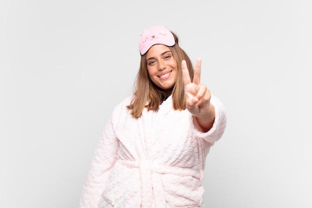 Jeune femme, porter, pyjama, sourire, et, à, amical, montrer, numéro deux, ou, seconde, à, main, avance