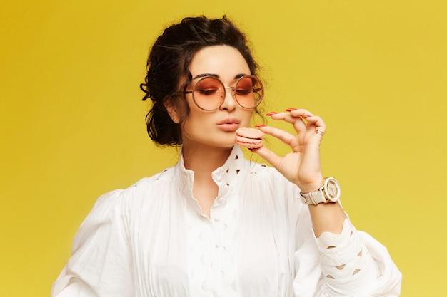 Jeune femme, porter, robe blanche, manger, biscuit macaron, isolé, sur, mur jaune, à, espace copie