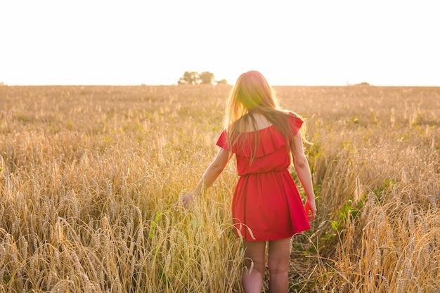 Jeune femme, porter, robe rouge, à, champ été, vue dos
