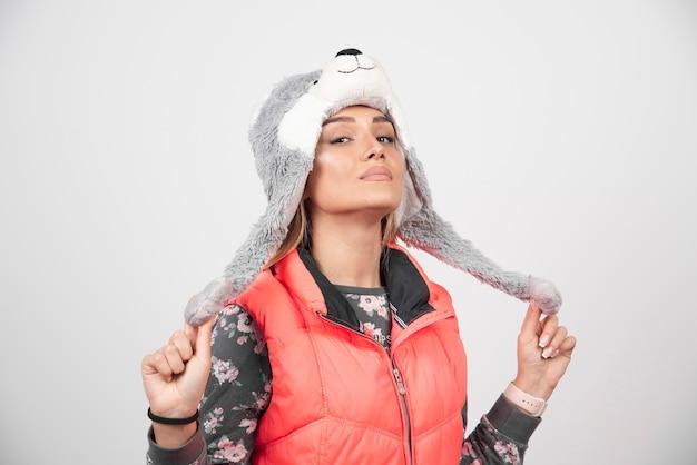 Jeune femme posant avec un chapeau drôle sur un mur blanc.
