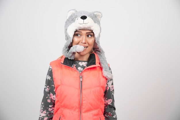 Jeune femme posant avec un chapeau drôle sur un mur blanc