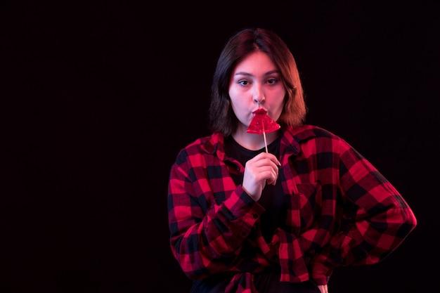 Jeune femme posant avec chemise à carreaux rouge et noir