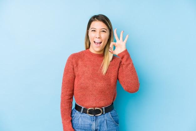 Jeune femme posant un clin d'œil et détient un geste correct avec la main