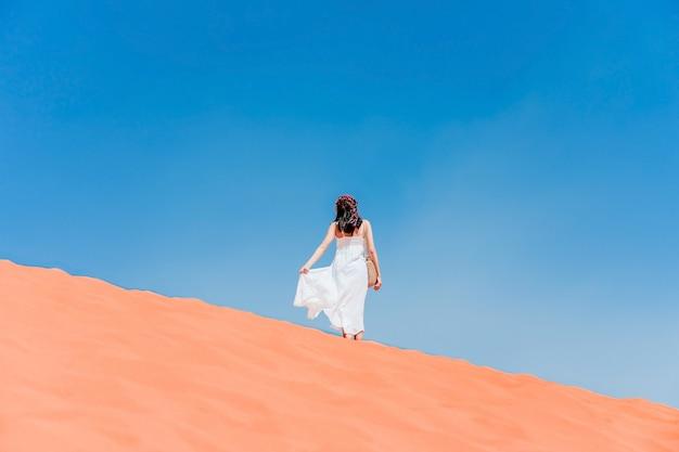 Une jeune femme posant sur la crête d'une dune de sable rouge dans le désert de wadi-rum, jordanie