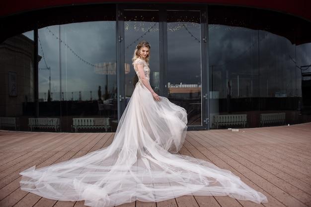 Jeune femme posant dans une robe de mariée blanche