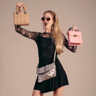 Une jeune femme posant dans une robe noire et des sacs à main
