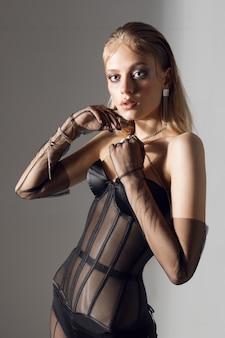 Jeune femme posant dans un studio photo, femme à la mode en collants copron et corset. photo de haute qualité