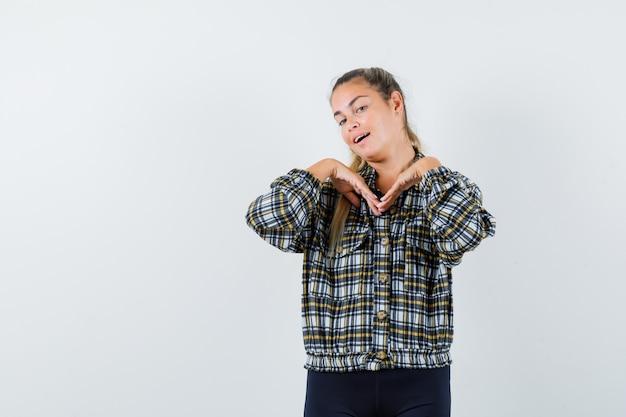 Jeune femme posant debout en chemise, short et à la recherche captivante. vue de face.