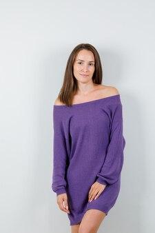 Jeune femme posant debout en chemise violette et à la fascination. vue de face.
