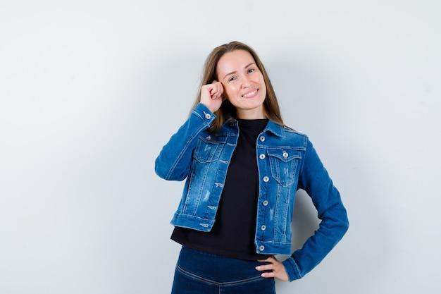 Jeune femme posant debout en chemisier, veste et charmante. vue de face.