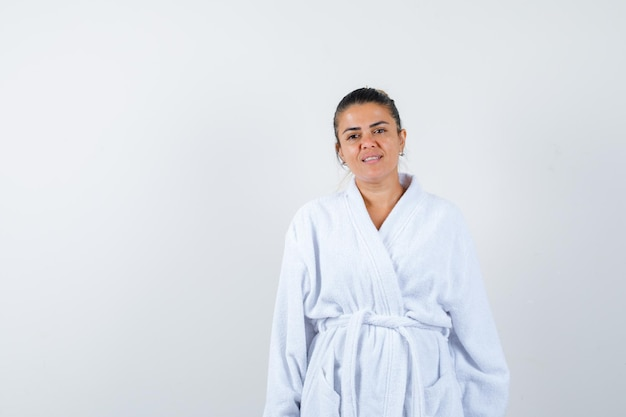 Jeune femme posant debout en peignoir et à l'air confiant