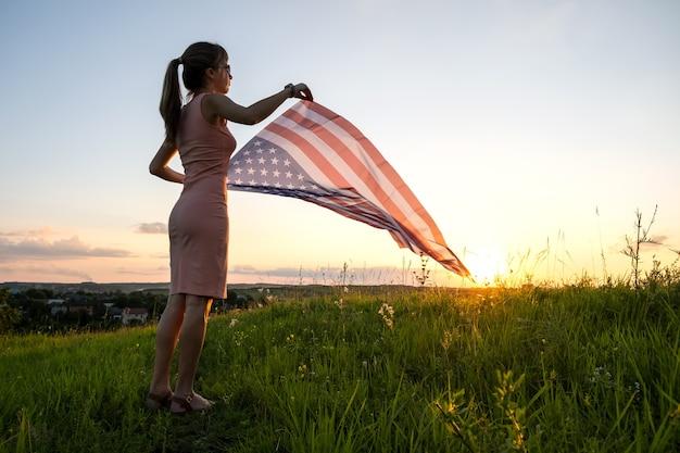 Jeune femme posant avec le drapeau national des états-unis à l'extérieur au coucher du soleil.