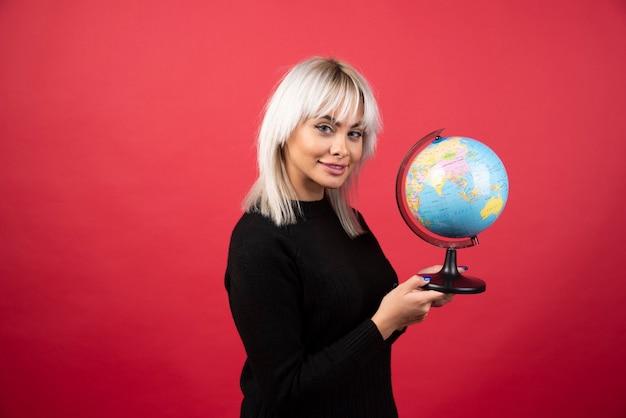 Jeune femme posant avec un globe sur fond rouge. photo de haute qualité