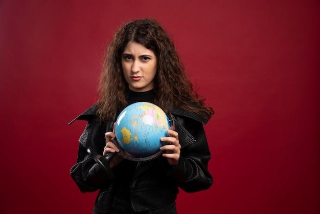 Jeune femme posant avec globe.