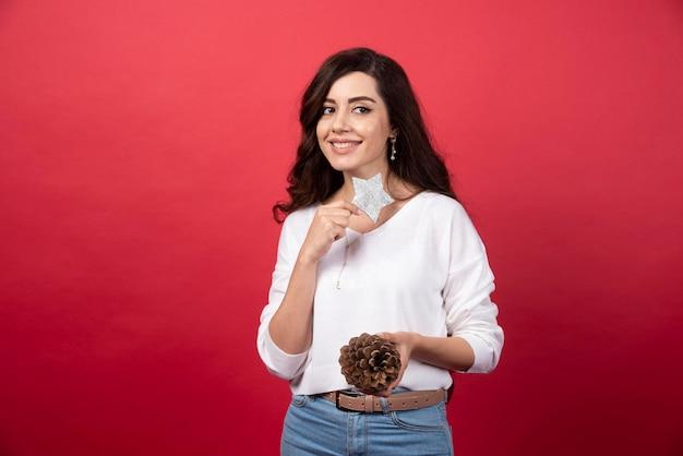 Jeune femme posant avec une grosse pomme de pin de noël et une étoile sur fond rouge. photo de haute qualité