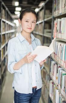 Jeune femme posant avec un livre dans la bibliothèque
