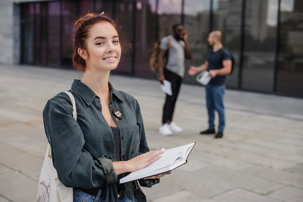 Jeune femme posant avec un livre