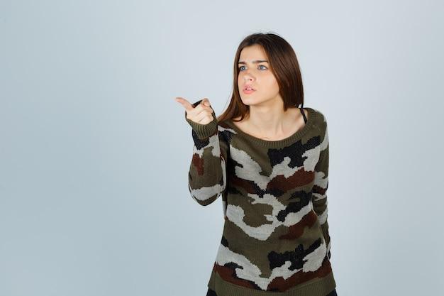 Jeune femme posant loin en pull et à l'ennui